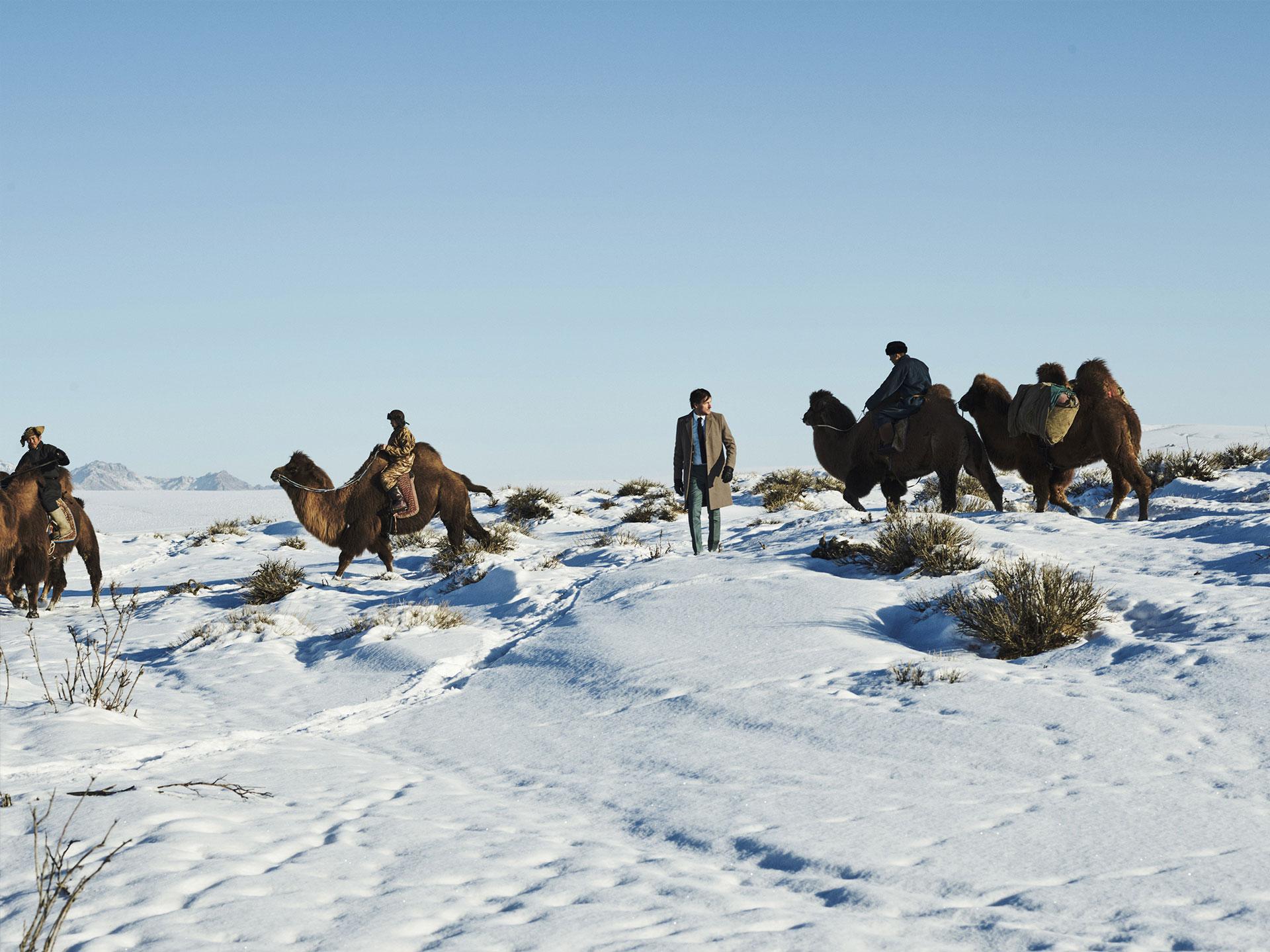 Floris loopt door de omringt door een karavaan aan kamelen